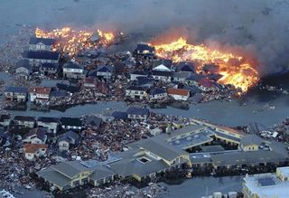Houses_swept_out_to_sea_burn_following_a_tsunami_and_earthquake_in_natori_city_in_northeastern_japan